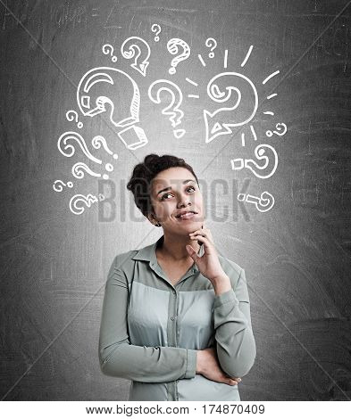 Portrait of a beautiful African American woman thinking about a brilliant idea while standing near a blackboard with a bunch of question marks attacking.