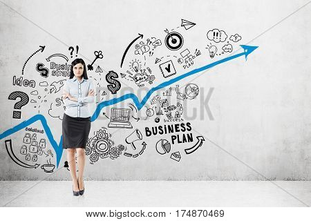 Portrait of a black haired businesswoman standing near a concrete wall with a blue graph and a business plan sketch depicted on it.