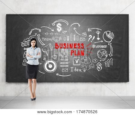 Portrait of a black haired woman standing with crossed arms near a blackboard with a white and red business plan sketch on it.