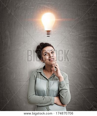 Portrait of a beautiful African American woman thinking about a brilliant idea while standing near a blackboard with a glowing light bulb above her.