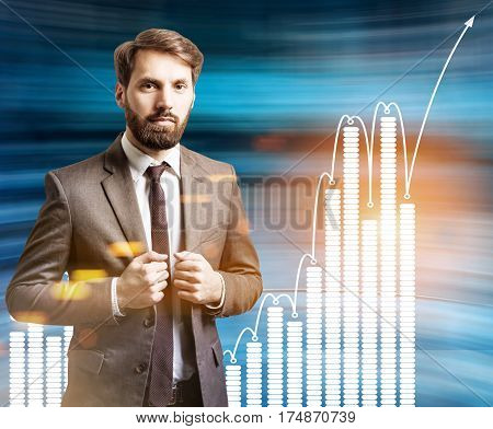Portrait of a serious bearded businessman standing near a blurred blue wal with graphs drawn on ti. Toned image.