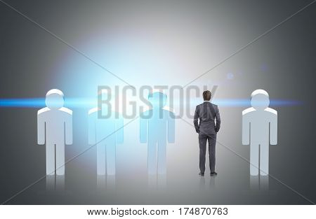 Schematic men figures standing in a row with a real businessman among them. Concept of hr and hiring a good candidate.
