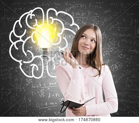 Portrait of a teenage girl standing near a blackboard holding a small black notebook. There is a large brain and a bright light bulb sketch on it.