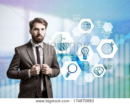 Portrait of a businessman with beard wearing a dark suit and standing in an office. There are hexagonal icons beside him. Double exposure.