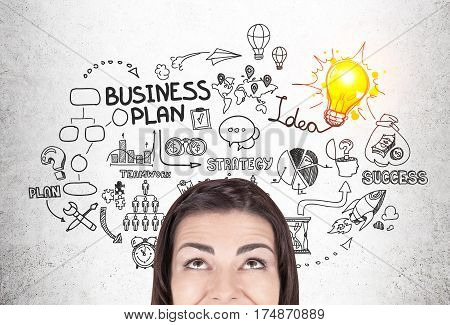 Close up of a black haired woman near a concrete wall with a light bulb and business plan icons on it.