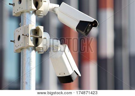 two white surveillance security cctv on steel pylon