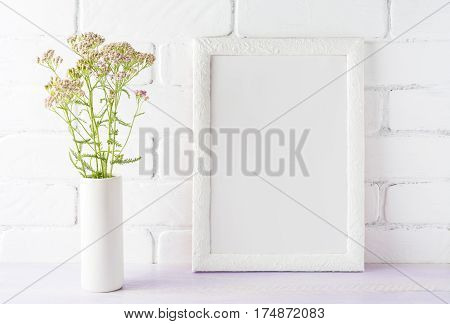 White frame mockup with creamy pink flowers in cylinder vase near painted brick wall. Empty frame mock up for presentation design. Template framing for modern art.