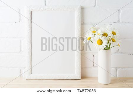 White frame mockup with daisy flower in styled vase near painted brick wall. Empty frame mock up for presentation design. Template framing for modern art.