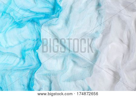 Bright background of crumpled gauze painted pale blue shades. Used in design for decor