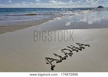 Hawaii Beach Aloha greeting written on Sand