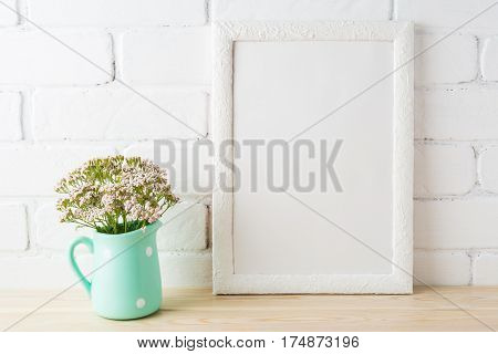 White frame mockup with wild very soft pink flowers in mint pitcher near painted brick wall. Empty frame mock up for presentation design. Template framing for modern art.