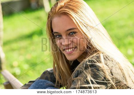 Smiling Girl Outdoors On A Bench