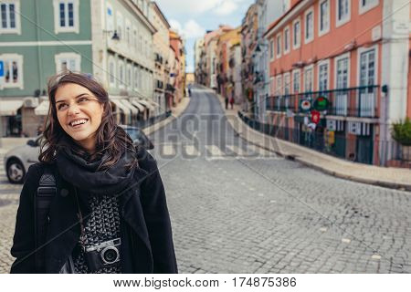 Enthusiastic traveler woman walking streets of european capital.Tourist in Lisbon,Portugal.Narrow, colorful,charming streets inviting curious woman tourist.Spending time and money traveling Europe