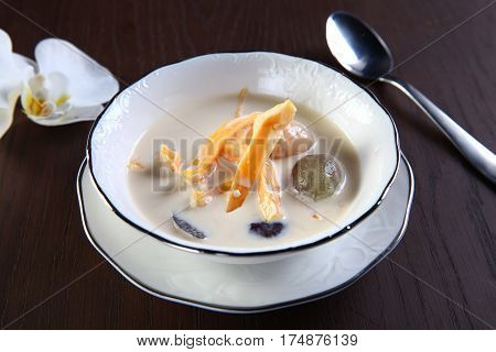 Sweet soup of mango and litchi on white bowl