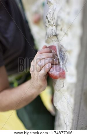 Young Man Climbing On Indoor Wall. Focus On The Hand