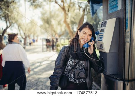 Smiling young woman speaking on a public payphone outside.Happy expression.Dialing local number in foreign country,low cost calls for international dials.Coin or card public phone used by tourist poster