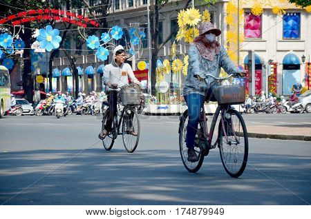 Vietnamese people riding bicycle on the road at Notre Dame Cathedral on January 22 2016 in Ho Chi Minh Vietnam