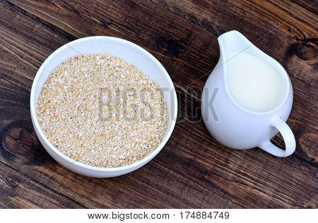 Oatmeal in a ceramic bowl and pitcher with milk on wooden table