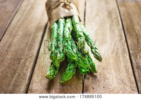 Bundle of fresh raw green organic asparagus tied with twine on plank wood kitchen table in backlighting closeup