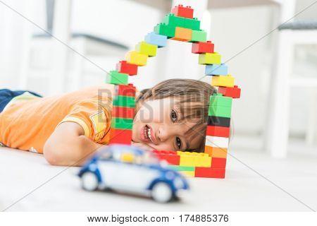 Little cute kid making a new dream home with a car