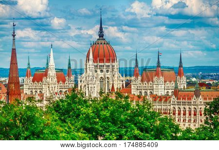 Hungarian parliament building at Danube river in Budapest city, Hungary. Blue sky with clouds and green tree leaves.