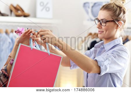 Female customer receiving shopping bags in boutique