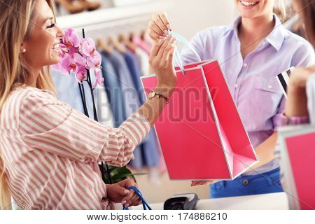 Closeup mid section of female customer receiving shopping bags in boutique