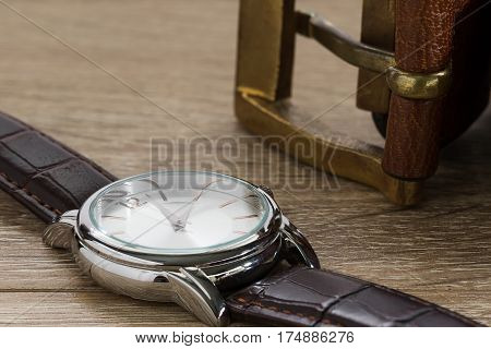 Close up wristwatch and brown leather belt on wood table