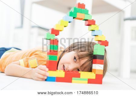 Little cute kid making a new dream home with a car