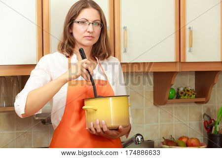 Housewife mixing soup meal dinner. Middle aged woman holding spoon ladle and pot. Housekeeper wearing orange apron preparing food.