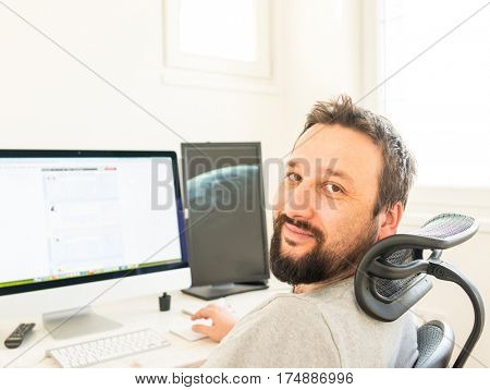 Designer worker on destop computer screens with working space background interior in office