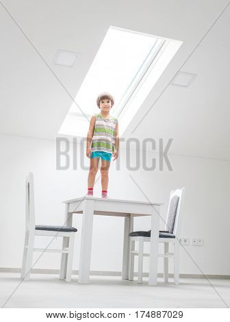 Happy child at home standing under roof window having dreams