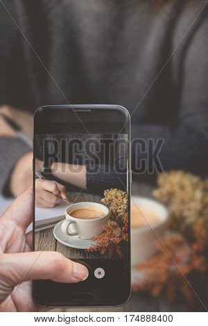 Taking a photo by Finger Pressing on Smartphone for Photograph Close up Other Hot Coffee on wooden in Social and Meeting with Coffee Concept Image for Coffee Advertise or Social Media with Drink Concept