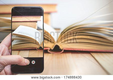 Taking a photo by Finger Pressing on Smartphone for Photograph Open book with copy space. Image for education and technology social media concept