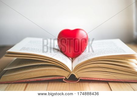 red heart on open book with copy space in relaxation and cozy mood Image for education love and brightness concept