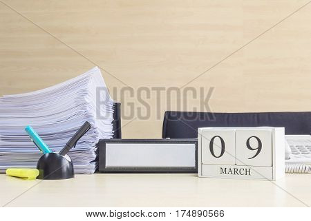 Closeup white wooden calendar with black 9 march word on blurred brown wood desk and wood wall textured background in office room view with copy space selective focus at the calendar