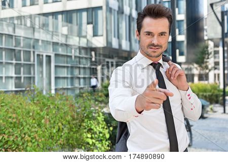 Portrait of angry businessman pointing at you outside office building
