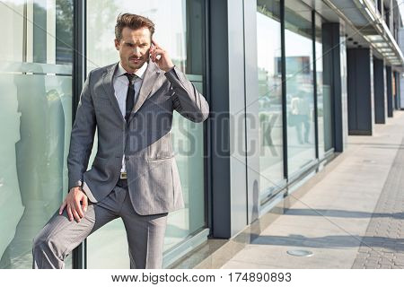 Young businessman using mobile phone outside office