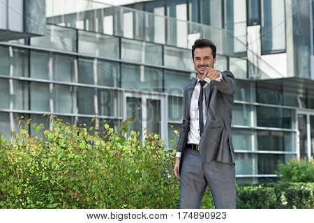 Portrait of happy young businessman pointing at you outside office building