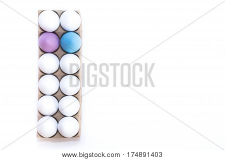 One Eastern egg dyed lavender, one blue egg and ten hard boiled white hen's eggs in a tan cardboard carton from above against a white background.