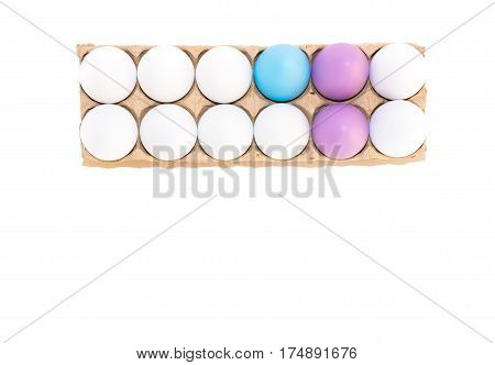 Two Easter eggs dyed lavender, one dyed blue and nine white hard boiled hen's eggs in a cardboard carton photographed from above against a white background with copy space.