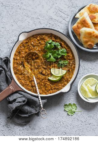 Cream coconut lentil curry and naan bread - healthy vegetarian food. On a grey background top view