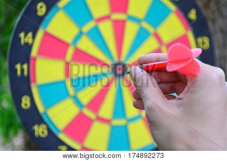 A hand holding a dart getting ready to aim at the dartboard