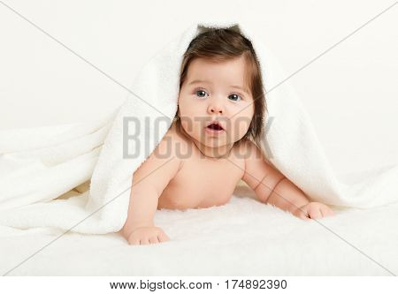Adorably baby lie on white towel in bed. Happy childhood and healthcare concept. Yellow toned