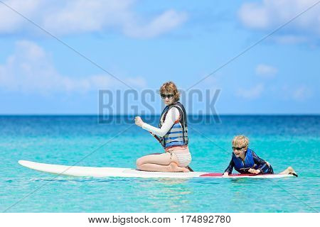 happy family of two young mother and her little son enjoying stand up paddleboarding in turquoise beautiful lagoon in caribbean healthy summer vacation activity