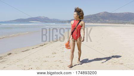 Female lifeguard walking along beach