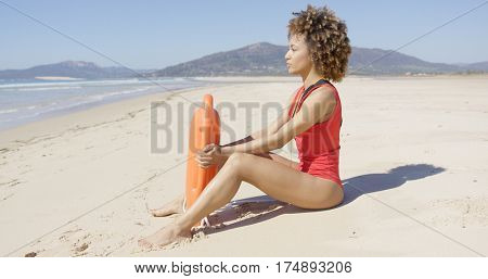 Lifeguard sitting with rescue float on beach