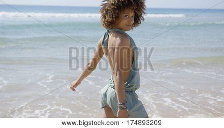 Female wearing summer jumpsuit posing on beach