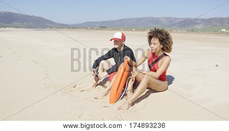 Female and male lifeguards patrolling beach