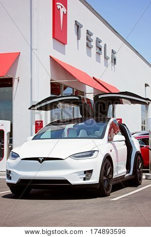 Seaside CA - May 29 2016: white tesla model x with falcon wing doors open charging at supercharger station